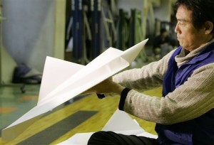 Takuo Toda, head of Japan Origami Airplane Association, folds a space shuttle-shaped paper plane at the Japan Airlines' facilities in Tokyo, Sunday, Feb. 3, 2008. Toda had nursed the idea of flying a shuttle-shaped paper plane since NASA launched its first spacecraft Enterprise in 1977. (AP Photo/Shizuo Kambayashi)